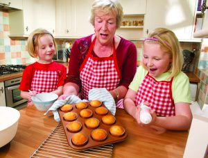 Senior woman and her two granddaughters smile while looking at freshly baked cupcakes.